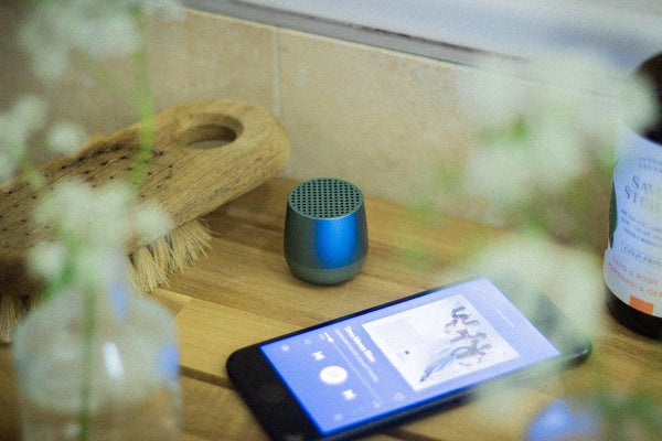 Small blue speaker on wooden shelf with phone playing music and bathroom products
