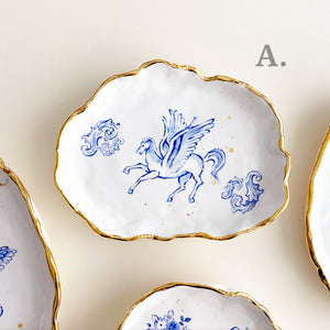 unique and delicate cherubs angel drawing plates. they are organic shaped handmade pottery. they are decorated with genuine gold rims.