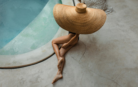 Girl laying by the pool wearing The Base Foundation on her legs in the shade Passionate from Baseofsweden