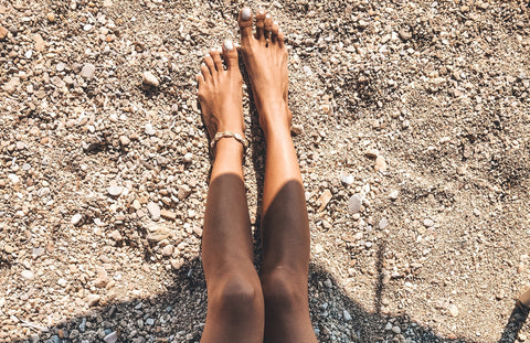 Legs in the sand wearing The Base Foundation