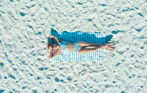 Woman laying on a big sandy beach wearing The Base Foundation