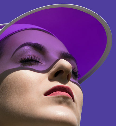 Girl in the sun wearing The Base Foundation shade Fresh with a purple background.