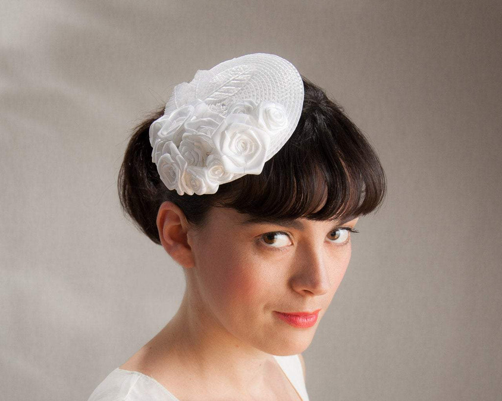 FASCINATOR - BRIDAL HEADPIECE WITH ROSES ON A BRAIDED BASE IN PURE WHITE AND OTHER SHADES © Seegang Berlin