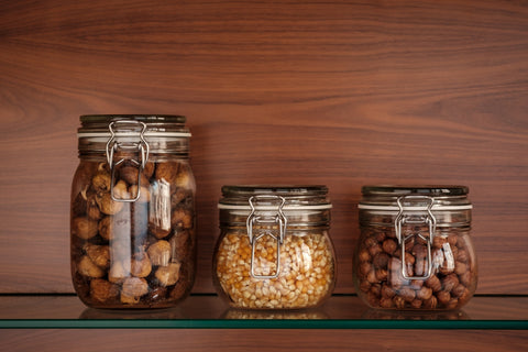 Mason jars lined up on a shelf with food in them