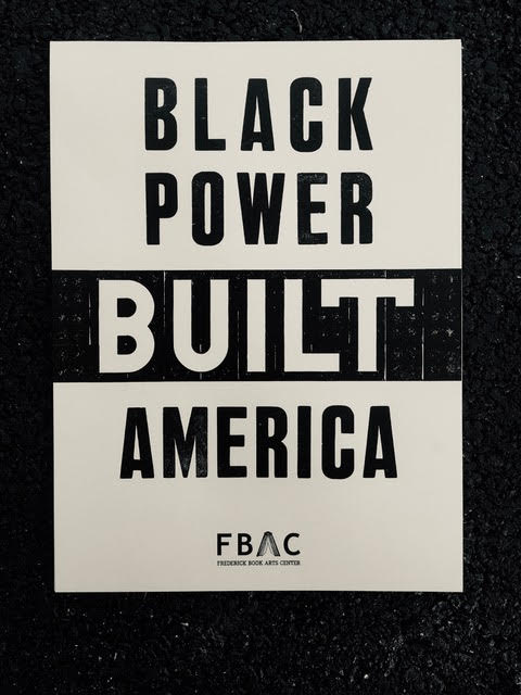 "White poster with the black words that reads ""Black Power Built America""."
