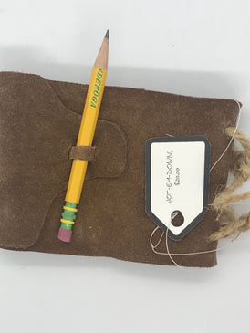 Brown leather journal clasped shut with a pencil.