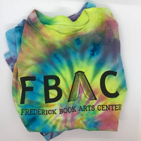 "Rainbow tie-dye t-shirt with the FBAC logo and ""Frederick Book Arts Center"" in black letters."