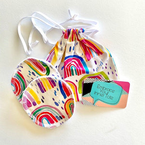 handmade breast pads in a bright rainbow fabric together with it's own travel/was tote
