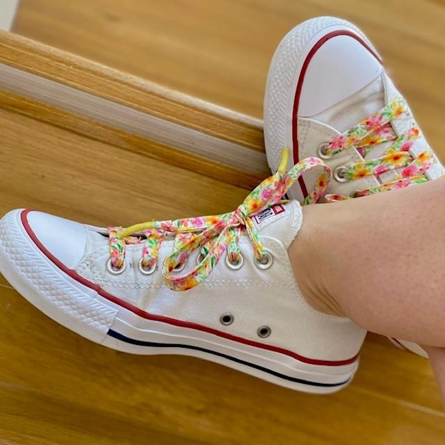 handmade shoelaces in a pink and yellow floral fabric worn on a white pair of converse sneakers