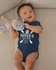 products/onesie-mockup-featuring-a-joyful-baby-boy-grabbing-his-stuffed-toy-25123.png
