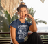 products/tee-mockup-of-a-woman-with-a-hair-bun-sitting-on-a-bench-by-the-beach-26863.png