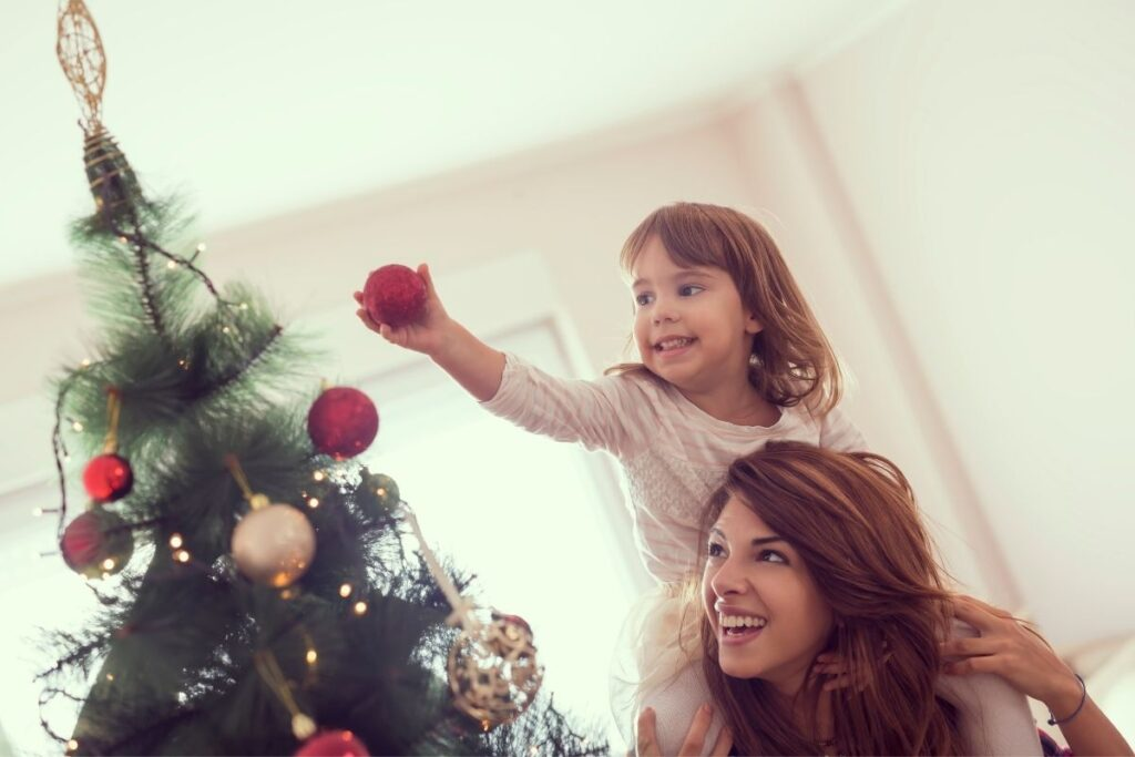 Mother carries daughter on shoulders so she can put a decoration on a Christmas tree.