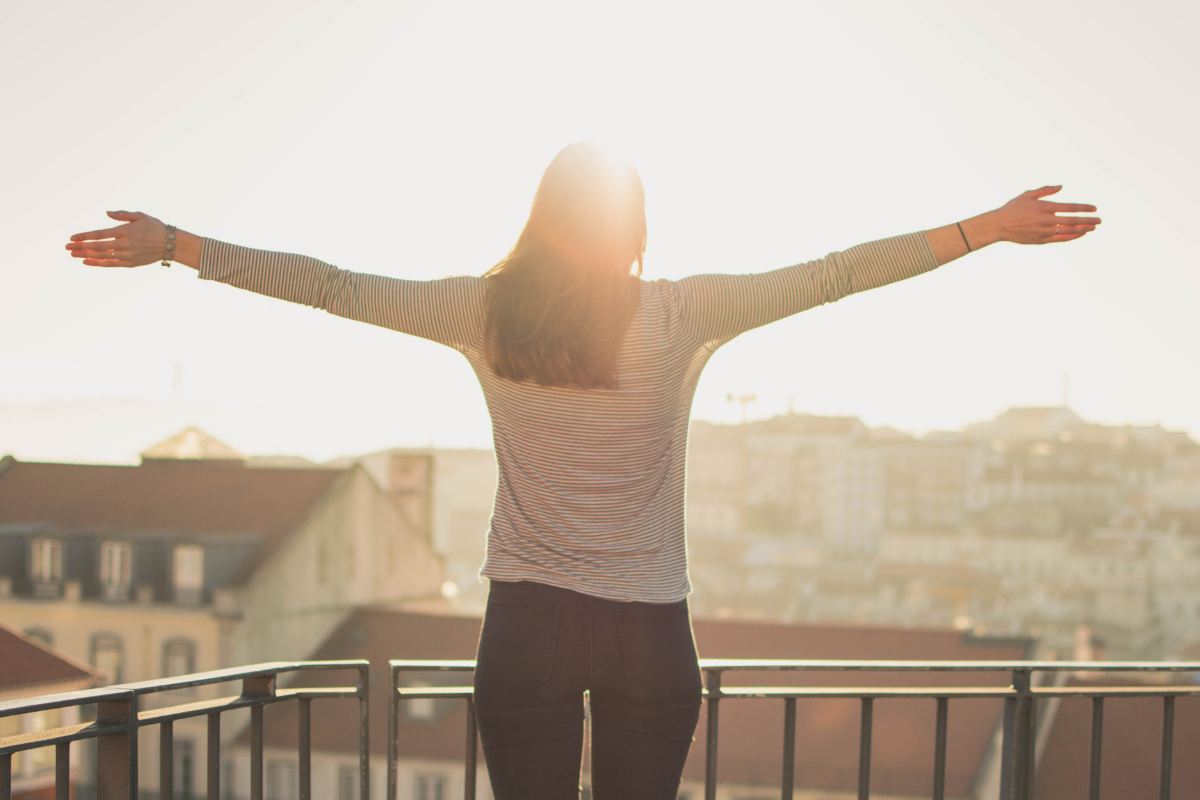 Woman standing in the sunshine, arms outstretched