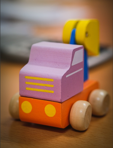 a colourful medical wooden car toy on a table