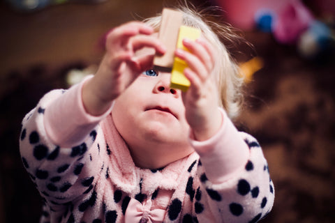 A 3-year-old girl playing with wooden blocks