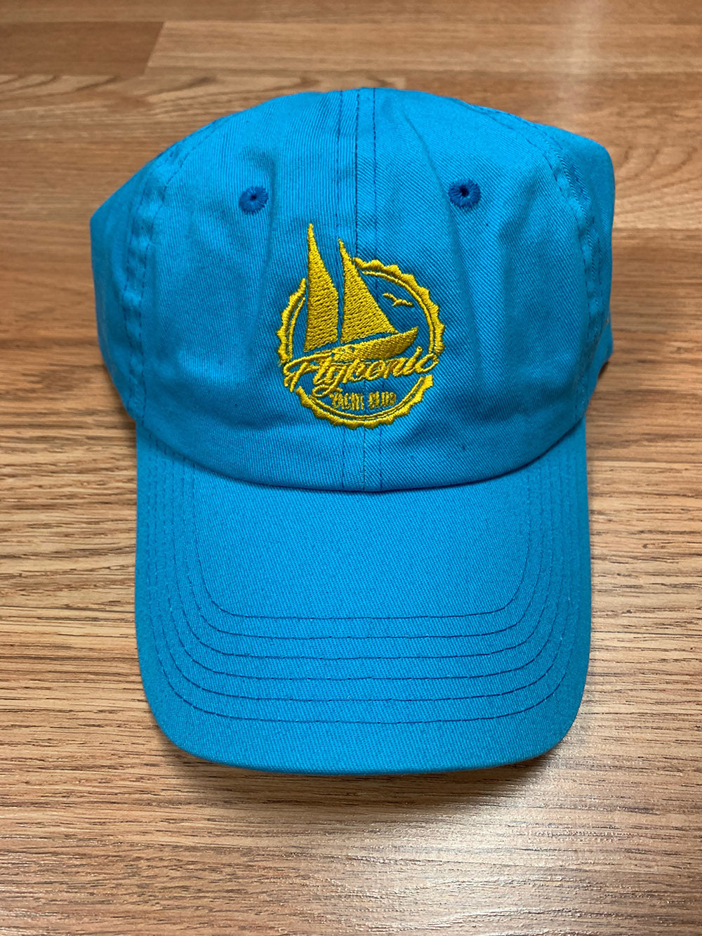 Flykonic Yacht Club Dad Hat on blue with yellow thread.