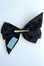 Back view of alligator clip on black eyelet lace hair bow.