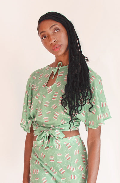 1930s inspired lightweight celery green keyhole neckline wrap top with novelty print.