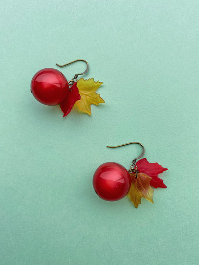 Shiny red bauble earrings with red and yellow leaf charms.