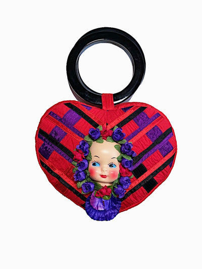 Kawaii baby doll face red heart purse with purple synthetic flowers and black circle handles.