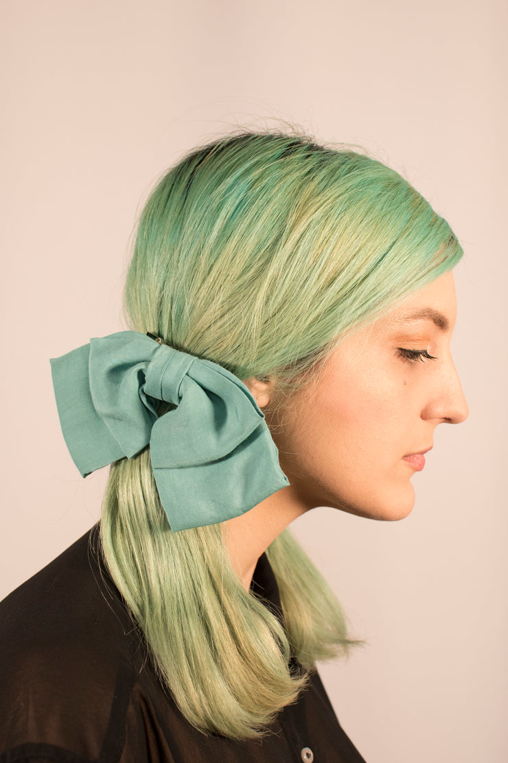 Cute dusty aqua green soft hair bow on model.