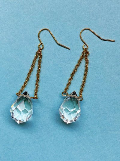 Teardrop faceted crystal drop earrings with gold chains.