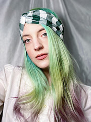 Retro style twist front forest green gingham headband on model.