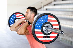 Male weightlifter in front rack position with American flag bumper plates on a barbell