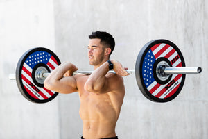 Shirtless male weightlifter in in front rack postion of his lift while using the red, white, and blue American flag bumper plates on his bar