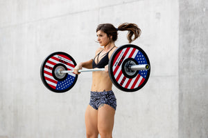 Female weightlifter executing a clean with red, white, and blue American flag bumper plates on a bar
