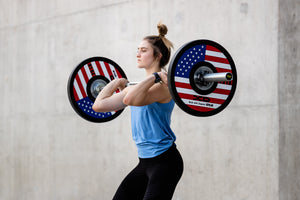 Female weightlifter in front rack receiving position while use the red, white, and blue American flag bumper plates