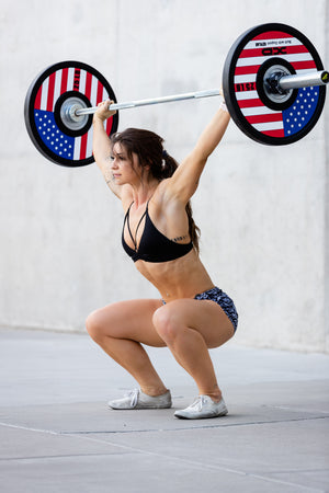 Female weightlifter executing a overhead squat with red, white, and blue American flag bumper plates on a bar