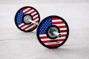 Weightlifting bar loaded with red, white, and blue American flag bumper plates on the ground