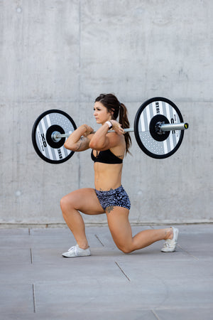 Female weightlifter executing a lunge with black, white, and grey American flag bumper plates on a bar