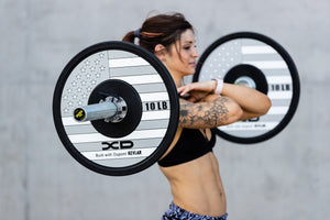 Female weightlifter executing a front squat with black, white, and grey American flag bumper plates on a bar