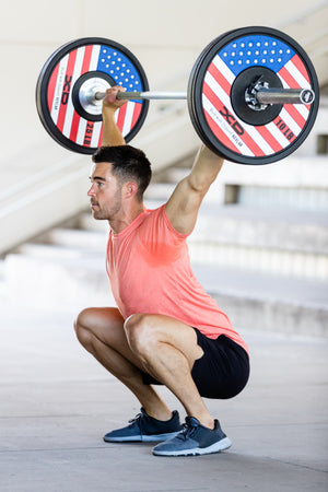 Male weightlifter in the bottom of a overhead squat lift with red, white, and blue American flag bumper plates on his bar