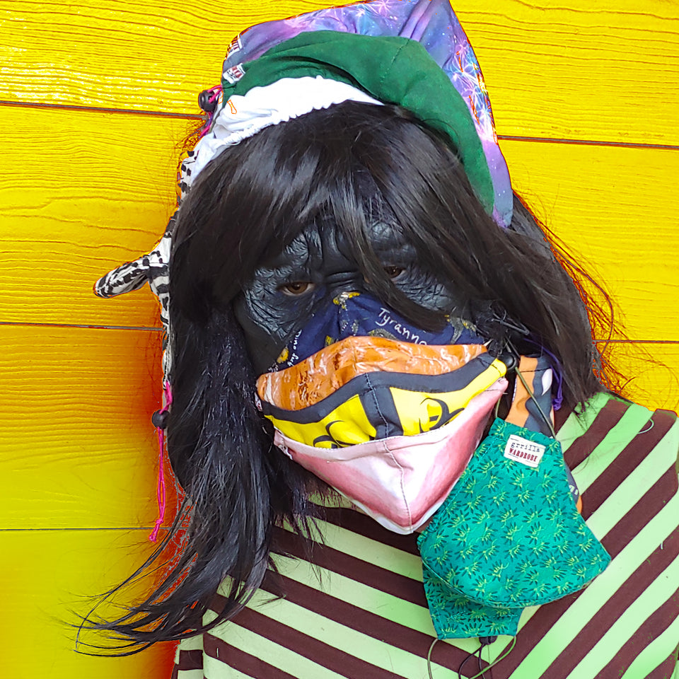 A closeup of the head and shoulders of a gorilla with long black hair and jaunty bangs is wearing four masks stacked on her face, two masks hanging from one ear, several more masks on top of her head, and another hanging from them.