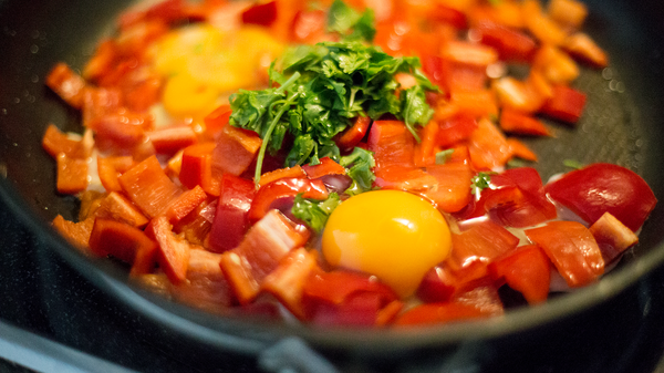 Mixing peppers, tomatoes and eggs