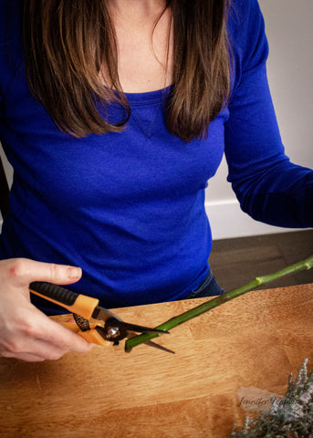 using pruners to cut roses