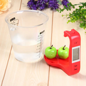 DIGITAL MEASURING CUP FEATURED ON A WOODEN BENCH, THE DIGITAL SCALE (RED) HAS BEEN DISMANTLED FROM THE MEASURING CUP AND THE SCALE IS WEIGHING TWO APPLES AND DISPLAYING THE WEIGHT ON THE LCD SCREEN