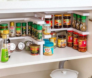 two adjustable spice racks set up with different settings side by side both stacked with an assortment of spices