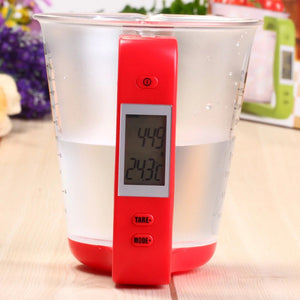 THE DIGITAL MEASURING CUP WITH RED HANDLE FEATURED ON A WOODEN TABLE, THE MEASURING CUP CONTAINS WATER AND THE LCD SCREEN IS DISPLAYING TEMPERATURE AND WEIGHT AND THE TARE AND MODE BUTTONS ON THE SIDE OF THE SCALE ARE CLEARLY VISIBLE