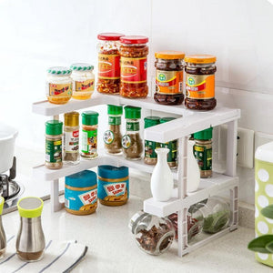 THE ADJUSTABLE SPICE RACK IN PLACE IN THE KITCHEN WITH AN ASSORTMENT OF DIFFERENT SPICES STACKED ON IT