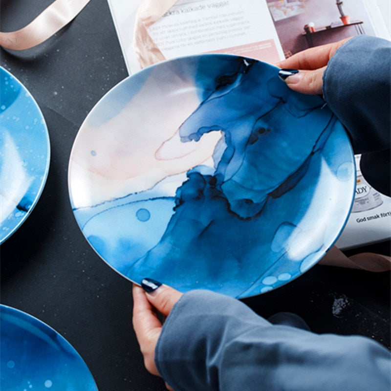 Person holding a plate with blue and white cloudy design