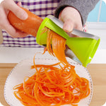 a person using the best zucchetti maker with a carrot to make noodles