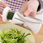 the zoodle maker featured in white being used by a person to make zucchini spaghetti