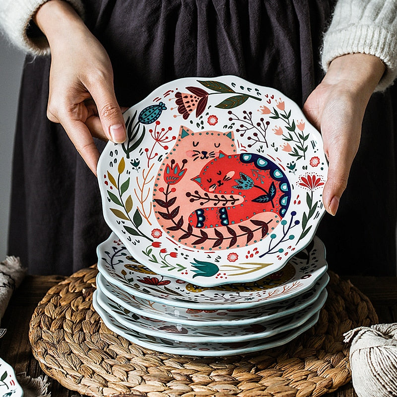 A PERSON SHOWING A STACK OF CAT PLATES, ONE PLATE FACING THE CAMEREA SHOWS THE DESIGN OF TWO CATS holding each other on like pink the other dark red, with flowers in the background