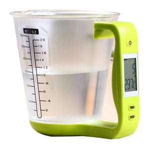 DIGITAL MEASURING CUP WITH GREEN HANDLE FEATURED ON A WHITE BACKGROUND, THE MEASURING CUP CONTAINS 10OZ OF WATER AND THE LCD SCREEN IS DISPLAYING THE WEIGHT AND TEMPERATURE OF THE WATER