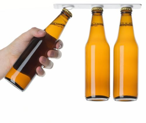The Magnetic bottle holder being used by someone, the person is grabbing the first bottle from the front of the magnetic strip while the other two bottles remain attached in place via the magnetic strip