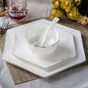 a small plate, large plate, bowl and spoon featured on dinning table